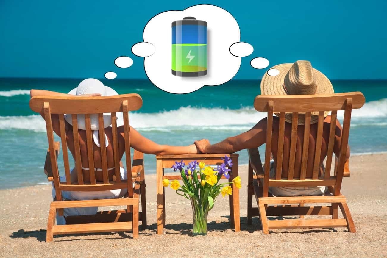 Casal descansando sobre cadeiras de praia em frente ao mar