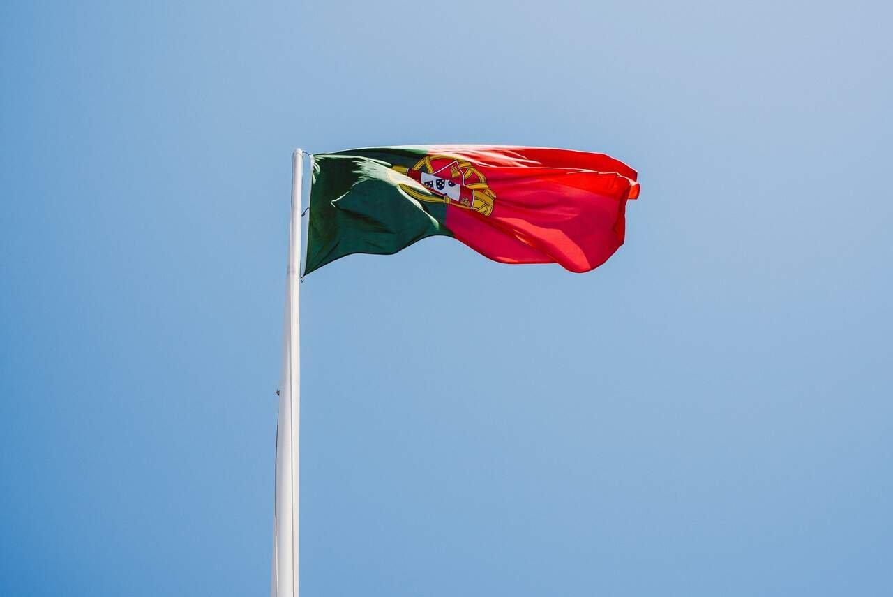 Bandeira de Portugal ao vento sob céu azul